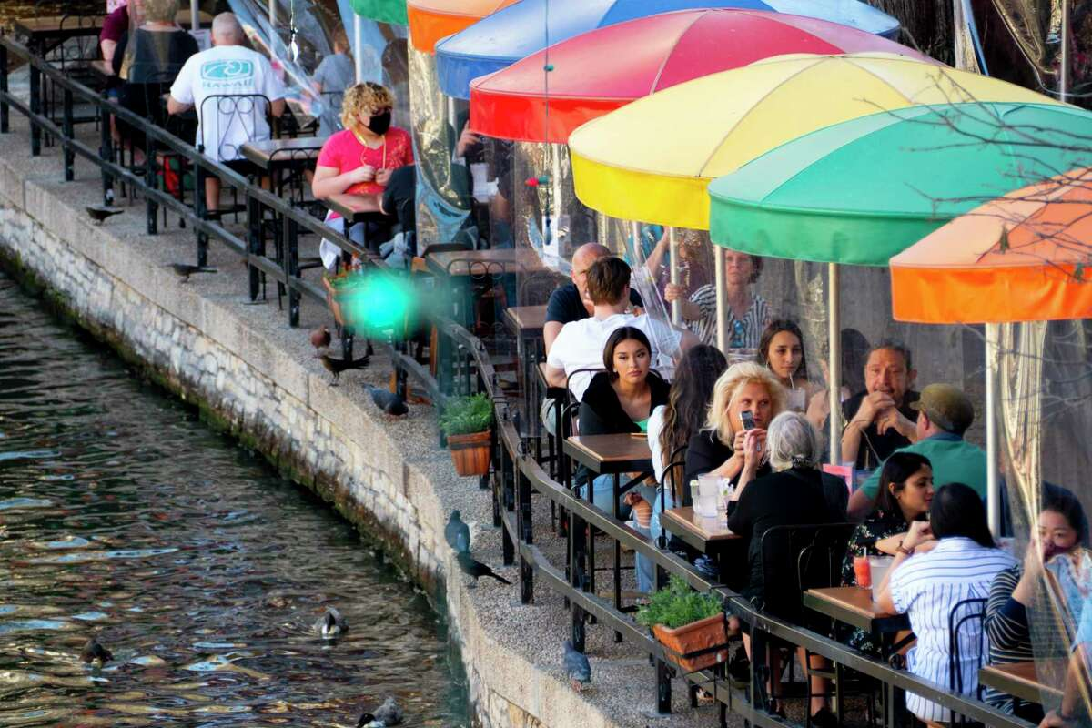People dine at Casa Rio on the River Walk on Friday, March 5, 2021. The tables are separated by clear partitions.