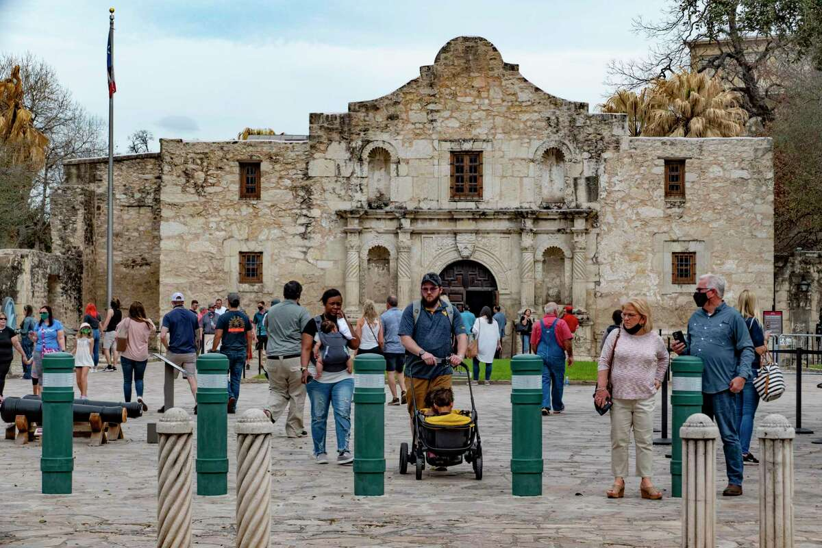 Some people wear masks and some do not as they tour the Alamo on Wednesday, March 10, 2021.
