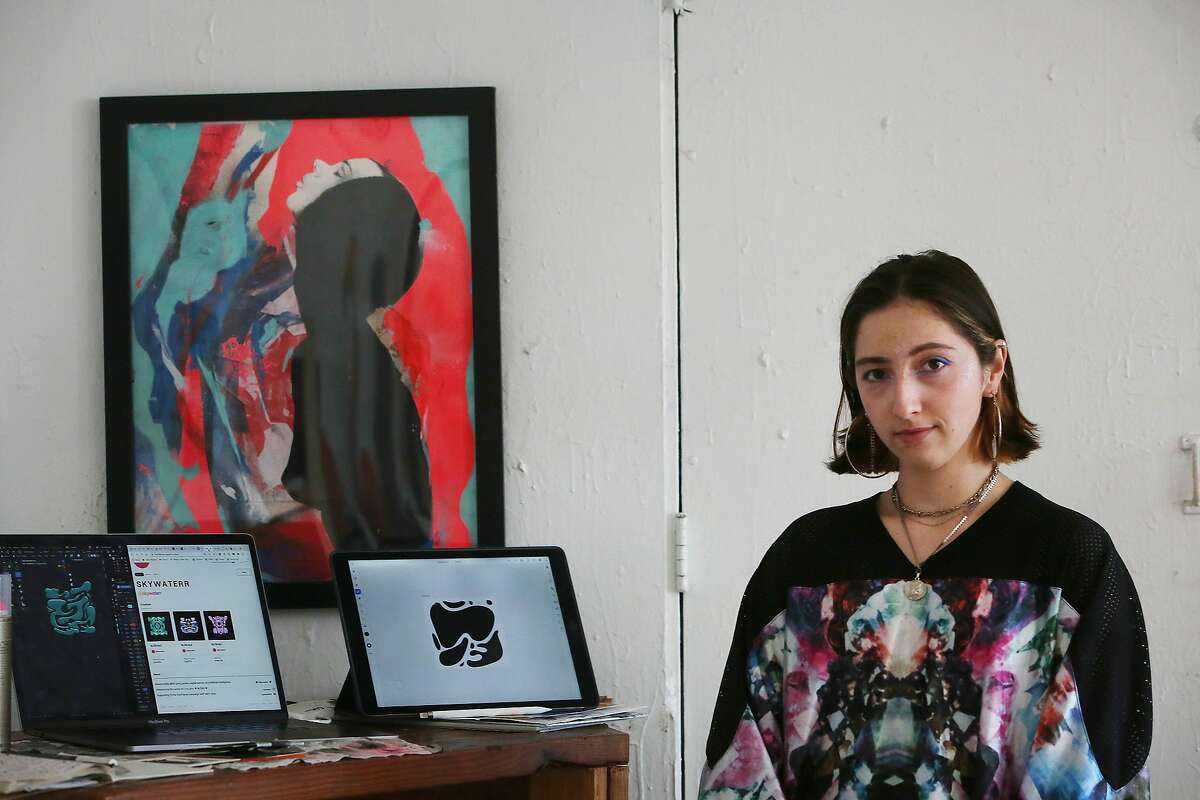 Mixed media artist Göksu Ilgaz Koçakcigill, also known as @skywaterr, stands for a portrait next to works of her digital art displayed on her laptop and tablet in her studio on Friday, March 12, 2021 in San Francisco, Calif.