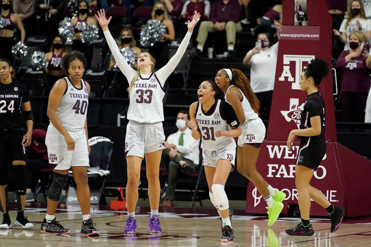 Texas A&M center Anna Dreimane (33) and forward N'dea Jones (31) react after time expires on a win during an NCAA college basketball game against South Carolina securing the Aggies first SEC regular-season championship on Sunday, Feb. 28, 2021, in College Station, Texas. (AP Photo/Sam Craft)