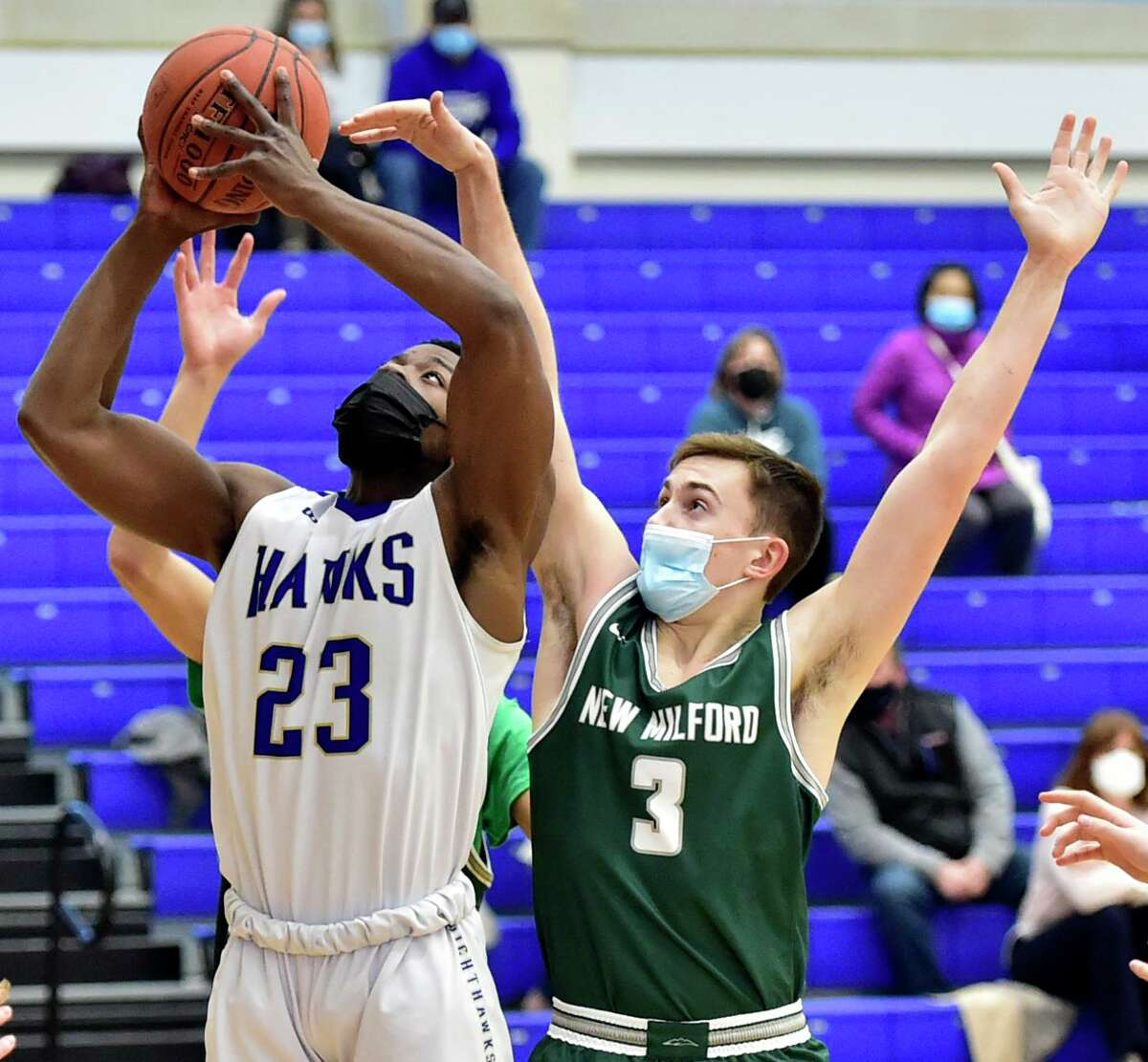 Newtown, Connecticut - Monday, March 15, 2021: Isaiah Williams of Newtown left, goes up for another shot after a rebound against Sam Tarrant of New Milford H.S. during the first quarter of basketball Monday at Newtown High School.