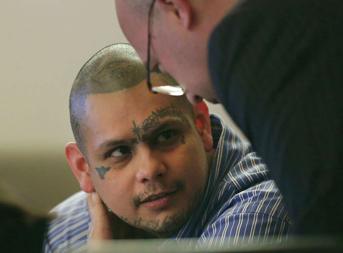 Gabriel Moreno, left, listens to his lawyer during his retrial on a murder charge in 2018. He was acquitted in the beating and suffocation death of Jose Luis Menchaca (and subsequent dismembering and burning of his body) but is in prison for possessing a weapon in jail. Now he has been charged with being part of a separate scheme to smuggle contraband into the jail.
