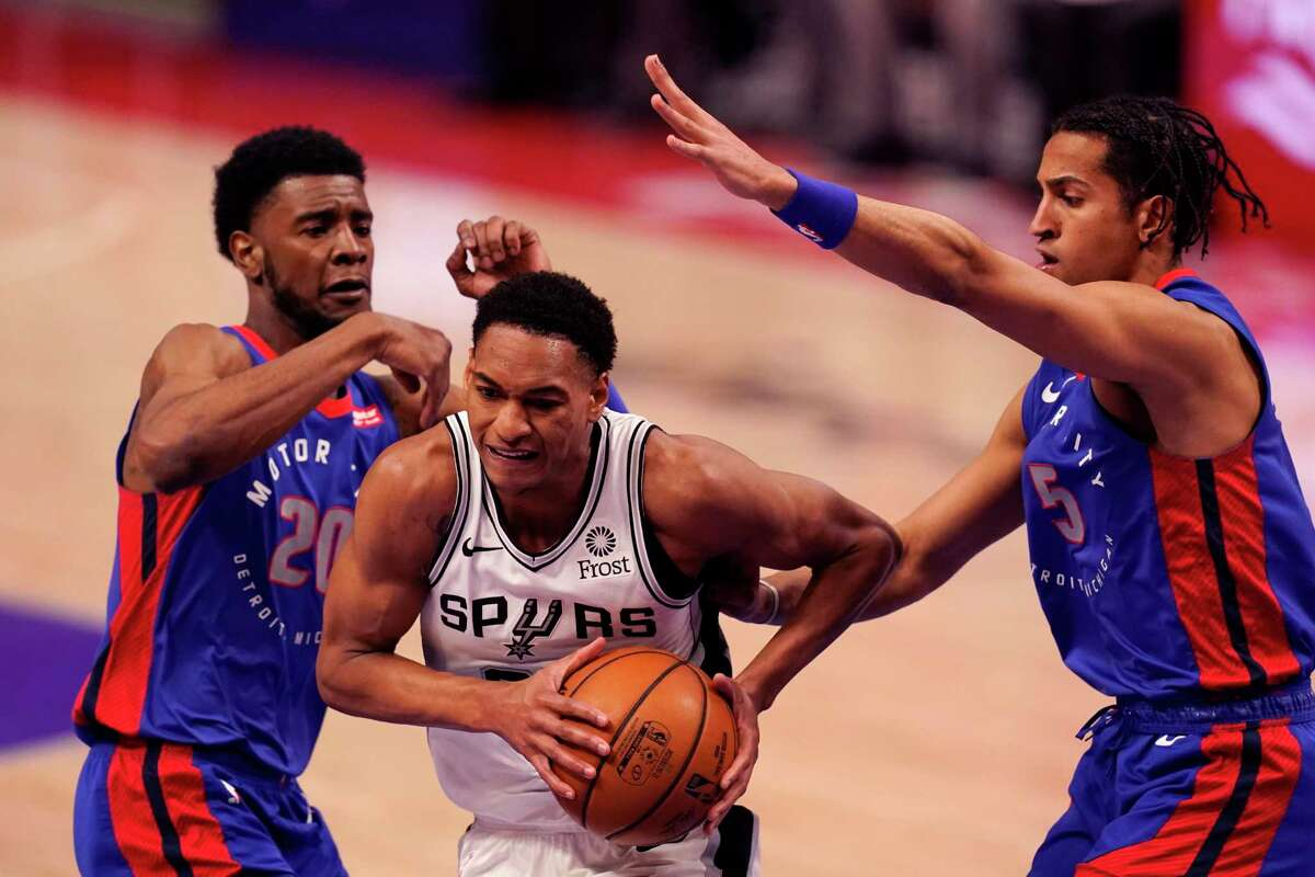 San Antonio Spurs guard Devin Vassell (24) drives between Detroit Pistons guard Josh Jackson (20) and guard Frank Jackson (5) during the second half of an NBA basketball game, Monday, March 15, 2021, in Detroit.