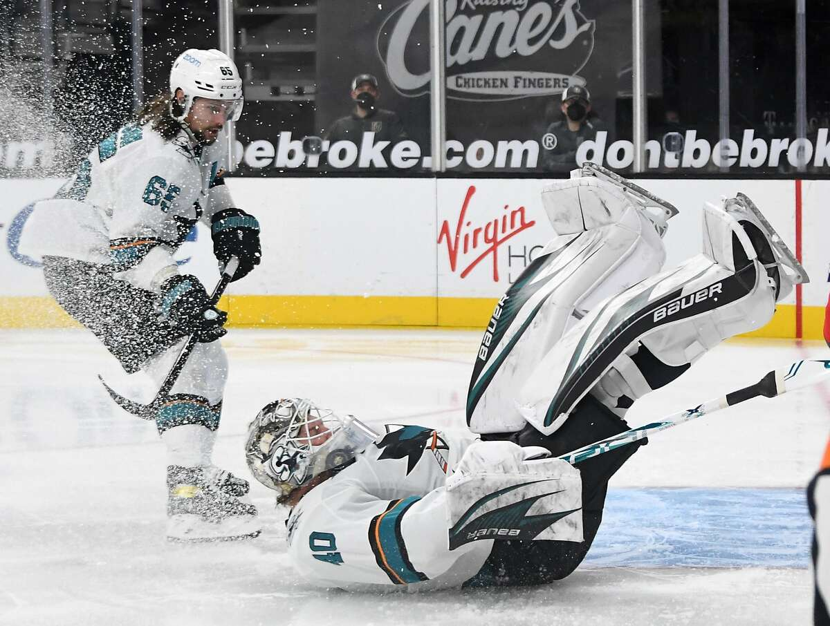Erik Karlsson of San Jose looks on as teammate gaolie Devan Dubnyk gets the puck caught in his throat protector.