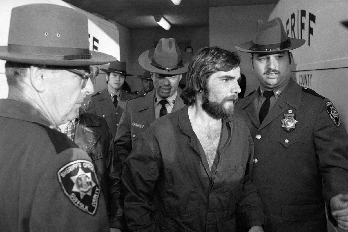 """In this Nov. 15, 1974 file photo, Ronald DeFeo Jr., center, leaves Suffolk County district court after a hearing, on New York's Long Island. DeFeo, the man convicted of slaughtering his parents and four siblings in a home that later inspired the book and movie """"The Amityville Horror"""" died Friday, March 12, 2021, at Albany Medical Center, where he was taken Feb. 2 from a prison in New York's Catskill Mountains, prison officials said Monday, March 15. He was 69."""