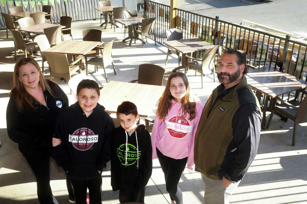 Owners Mathew and Kelly Calandro pose with their children, Bobby, Dominic and Ali on the recently completed outdoor dining patio at Caloroso Eatery and Bar, in Shelton, Conn. March 15, 2021.