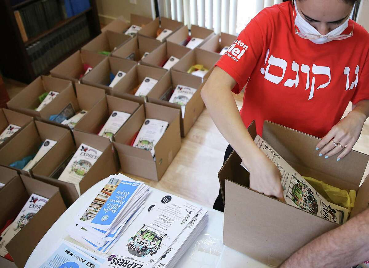 """Lior Ashkenazy Dor prepares a Passover """"survival kits"""" for students away from home at Houston Hillel on Friday, March 12, 2021. The kits include matzo, recipes, crafts, treats and a Haggadah."""