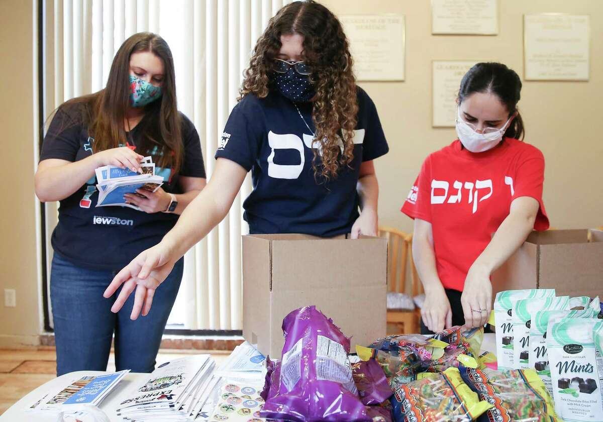 """Houston Hillel assistant executive director Alyssa Silva, from left, preps Passover """"survival kits"""" with Ellie Rips and Lior Ashkenazy Dor for students away from home on Friday, March 12, 2021. The kits include matzo, recipes, crafts, treats and a Haggadah."""