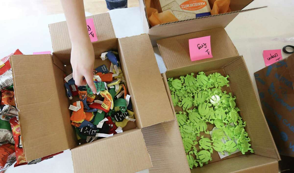 """A volunteer grabs from a box of plagues for a Passover """"survival kit"""" for a student away from home at Houston Hillel on Friday, March 12, 2021. The kits include matzo, recipes, crafts, treats and a Haggadah."""