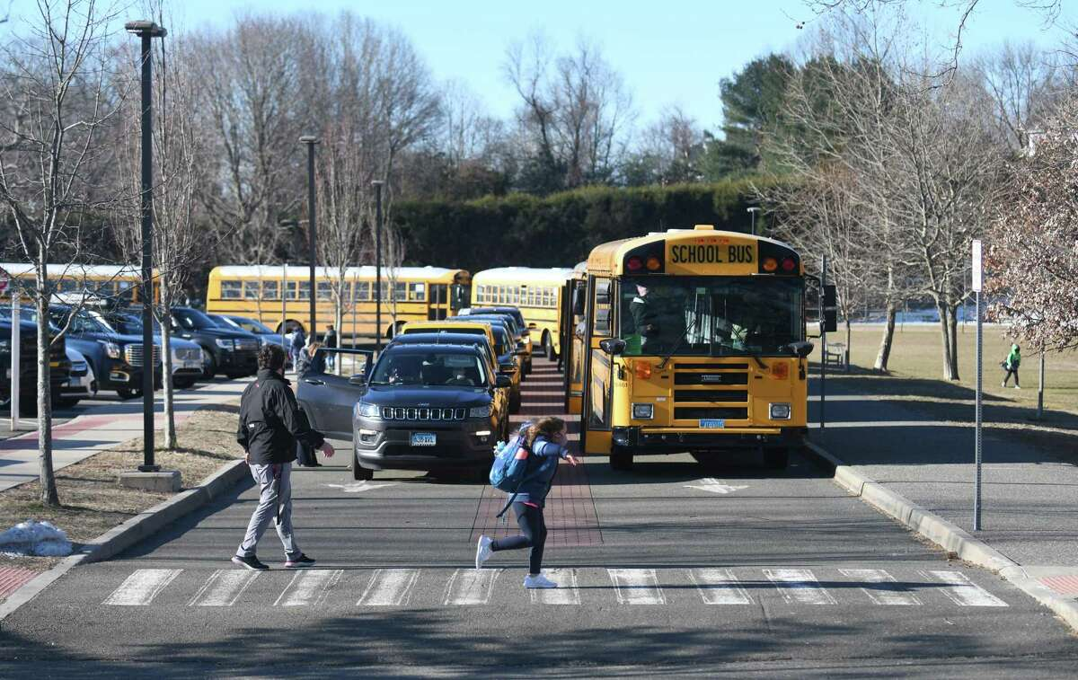 Students enter North Mianus School in the Riverside section of Greenwich, Conn. Tuesday, March 2, 2021.