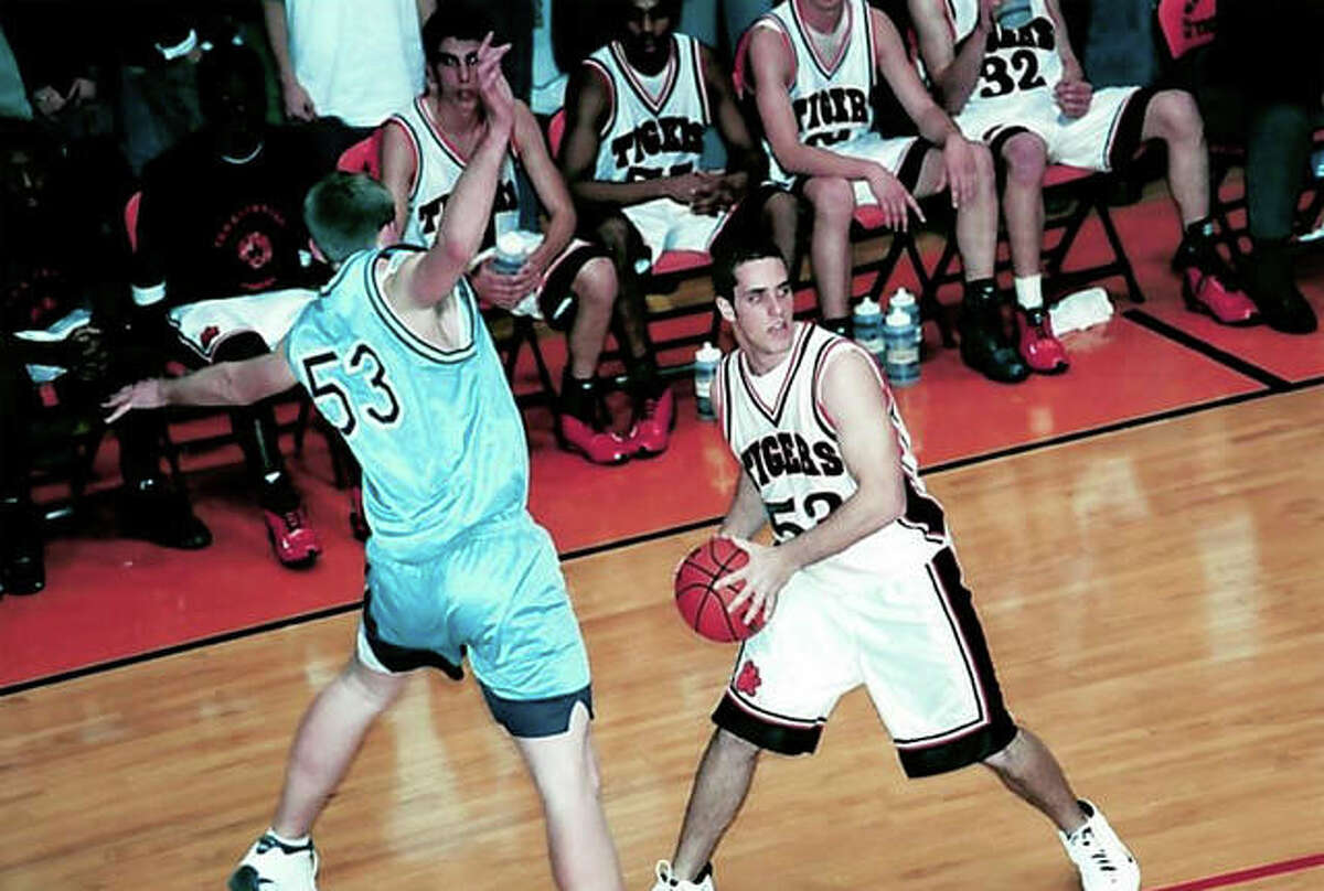 Edwardsville's Kevin Maliszewski, right, looks to pass the ball during his basketball playing days at EHS.