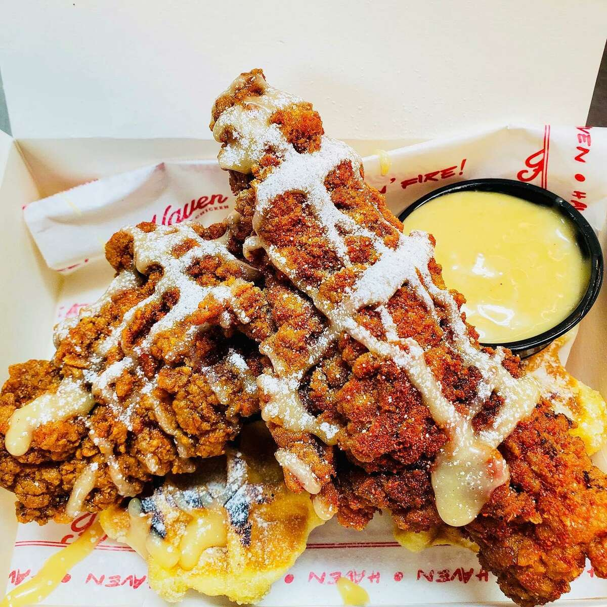 Haven Hot Chicken's chicken and waffles meal features two jumbo tenders with your choice of heat and a pair of Liege waffles, drizzled with maple brown-sugar aioli and dusted with powdered sugar.