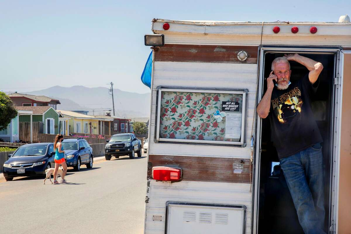 Jeffrey Allen Russell stands in the doorway of his RV parked on a residential street in Pacifica, Calif. Wednesday, May 27, 2020. Five Pacifica RV dwellers sued the city over its ban forbidding RVs to parked within city limits.