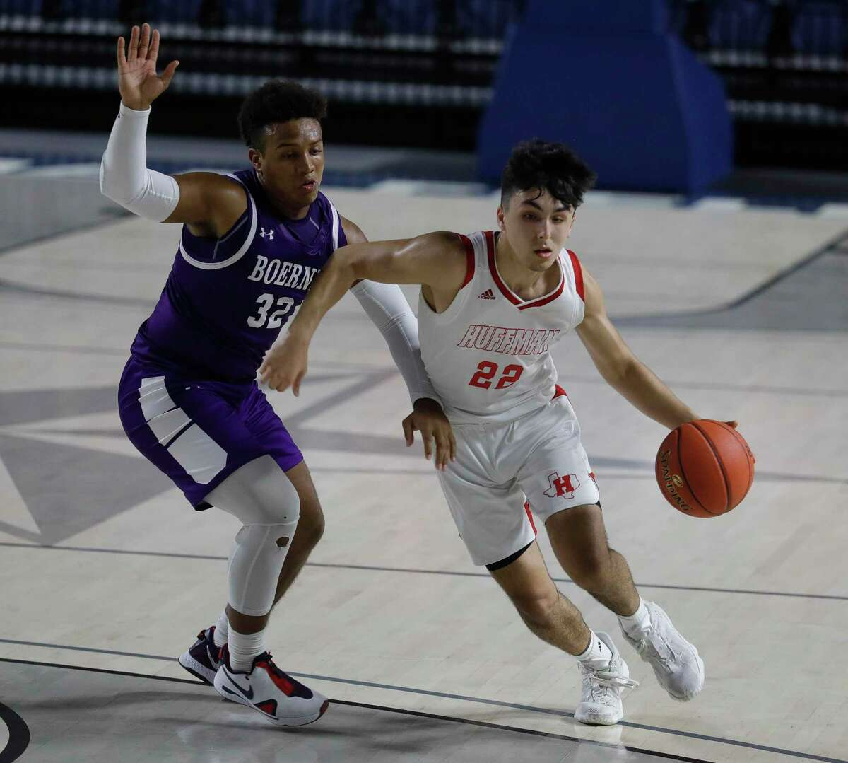 Huffman shooting guard Jesse Viramontez (22) drives the ball agaisnt Boerne guard Rashawn Galloway (32) during the first quarter of a Region III-4A state semifinal game at Delmar Fieldhouse, Tuesday, March 9, 2021, in Houston.