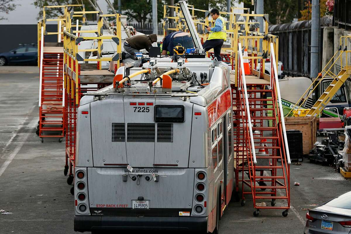 People work on a Muni bus at the Potrero Division yard on Dec. 5, 2018.