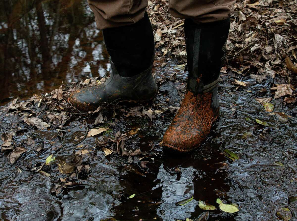 Texas Parks and Wildlife biologist Nate Fuller wears boots whenever entering the culvert to study tricolored bats. The use of boots makes it easier to clean and prevent the spread of white-nose syndrome to animals at other locations. Photographed Friday, March 12, 2021, north of Houston. Fuller specializes in the syndrome, which is a fungus that has been killing bats nationwide and is threatening bas in Texas as well.