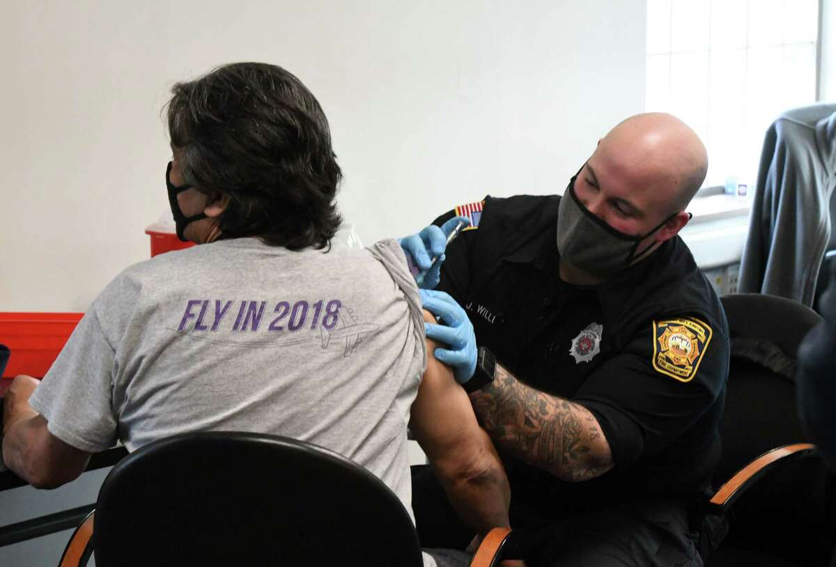 Albany International Airport firefighter Jake Willey administers COVID-19 vaccine to airport workers on Tuesday, March 16, 2021, at Albany International Airport in Colonie, N.Y. Albany County made 100 doses of the Pfizer vaccine available to the Albany County Airport Authority for distribution to employees. Starting Tuesday, April 6, everyone 16 years of age or older can make an appointment to get a COVID-19 vaccine - opening up vaccination in New York to everyone of any age regardless of health condition or job. (Will Waldron/Times Union)