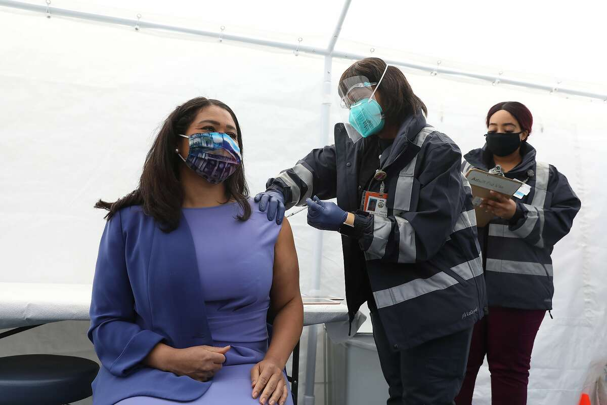 Kimberly Tucker (right), SFDPH nurse, gives Mayor London Breed (left) the Johnson and Johnson COVID-19 vaccine at a vaccine clinic at Maxine Hall Health Center on Tuesday in San Francisco. Tucker's daughter was a childhood friend of Mayor Breed.