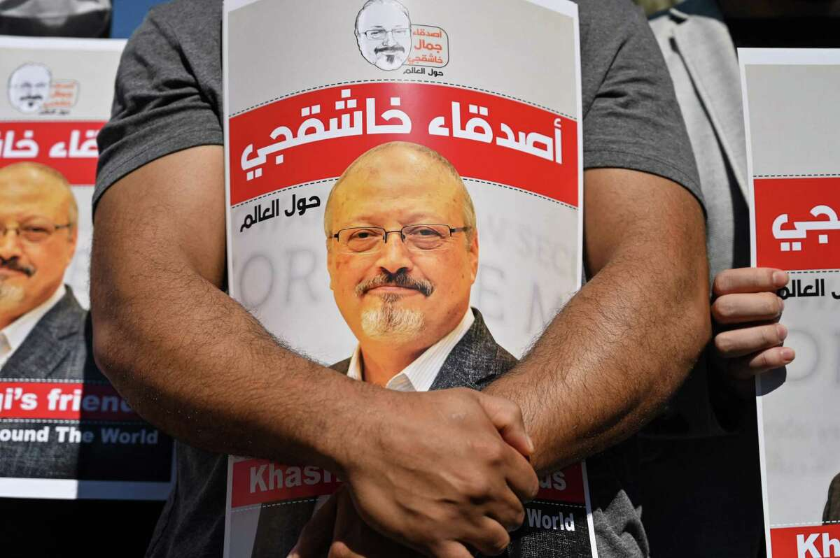 (FILES) In this file photo taken on October 02, 2020, friends of murdered Saudi journalist Jamal Khashoggi hold posters bearing his picture as they attend an event marking the second-year anniversary of his assassination in front of Saudi Arabia Istanbul Consulate. - The US director of national intelligence is expected to release a damning report on February 26, 2021, that fingers Saudi Crown Prince Mohammed bin Salman for the brutal murder and dismemberment of dissident journalist Jamal Khashoggi in October 2018. The classified report is believed to say that, based on intelligence collected by the CIA and other spy bodies, the kingdom's de facto leader directed the assassination of the respected US-based writer in the Saudi consulate in Istanbul. (Photo by Ozan KOSE / AFP) (Photo by OZAN KOSE/AFP via Getty Images)