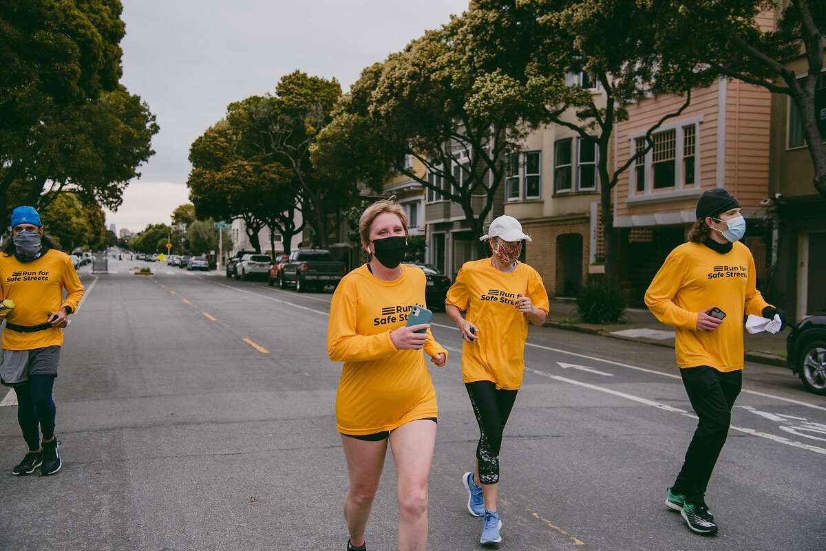Julie Nicholson smiles while running a half marathon marking the anniversary of her pedestrian crash on a slow street closed to car traffic in San Francisco, Calif., on Sunday, March 14, 2021. KNIGHT0317