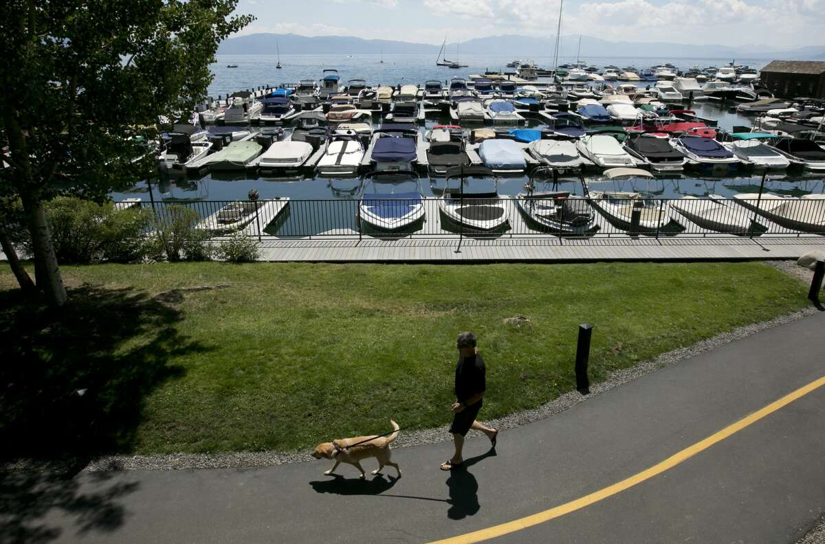 A pedestrian and a dog walk past the marina in Tahoe City in 2017. Businesses in North Tahoe are reopening, as an effort to organize a new district solidifies.