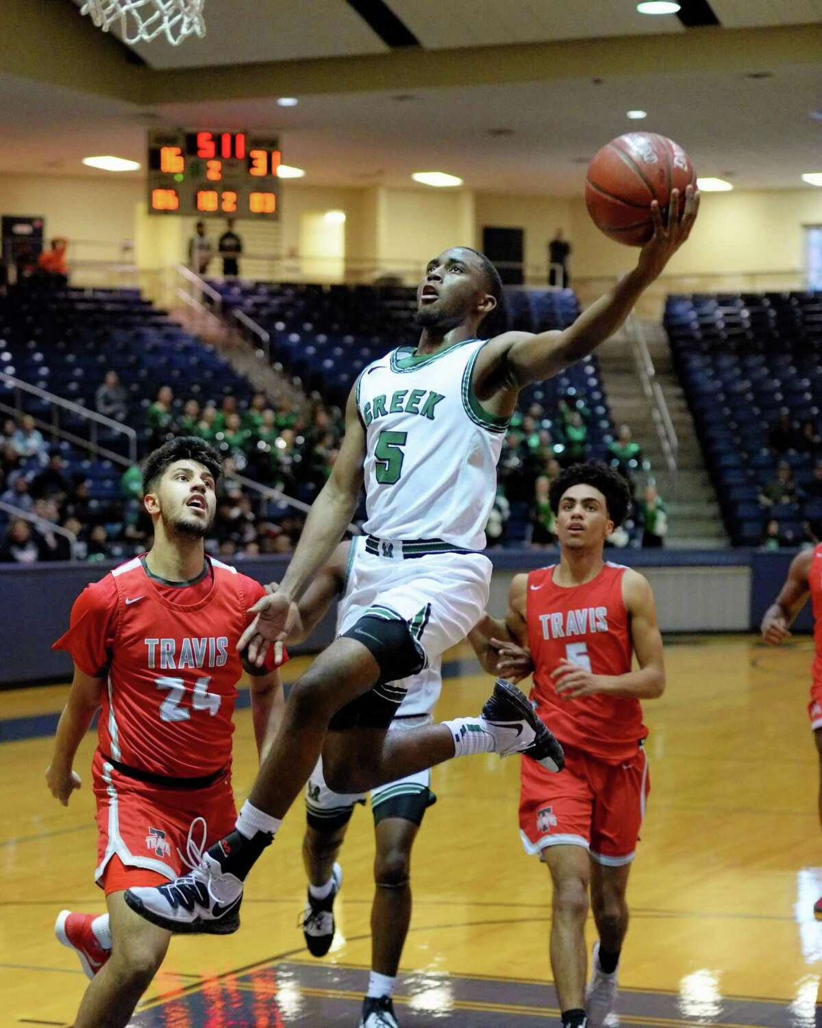 Jermon Washington (5) of Mayde Creek drives to the basket for a lay-up during the second quarter of a Boys 6A Region III Bi-District play-off game between the Mayde Creek Rams and the Travis Tigers on Tuesday, February 25, 2020 at Coleman Coliseum, Houston, TX.