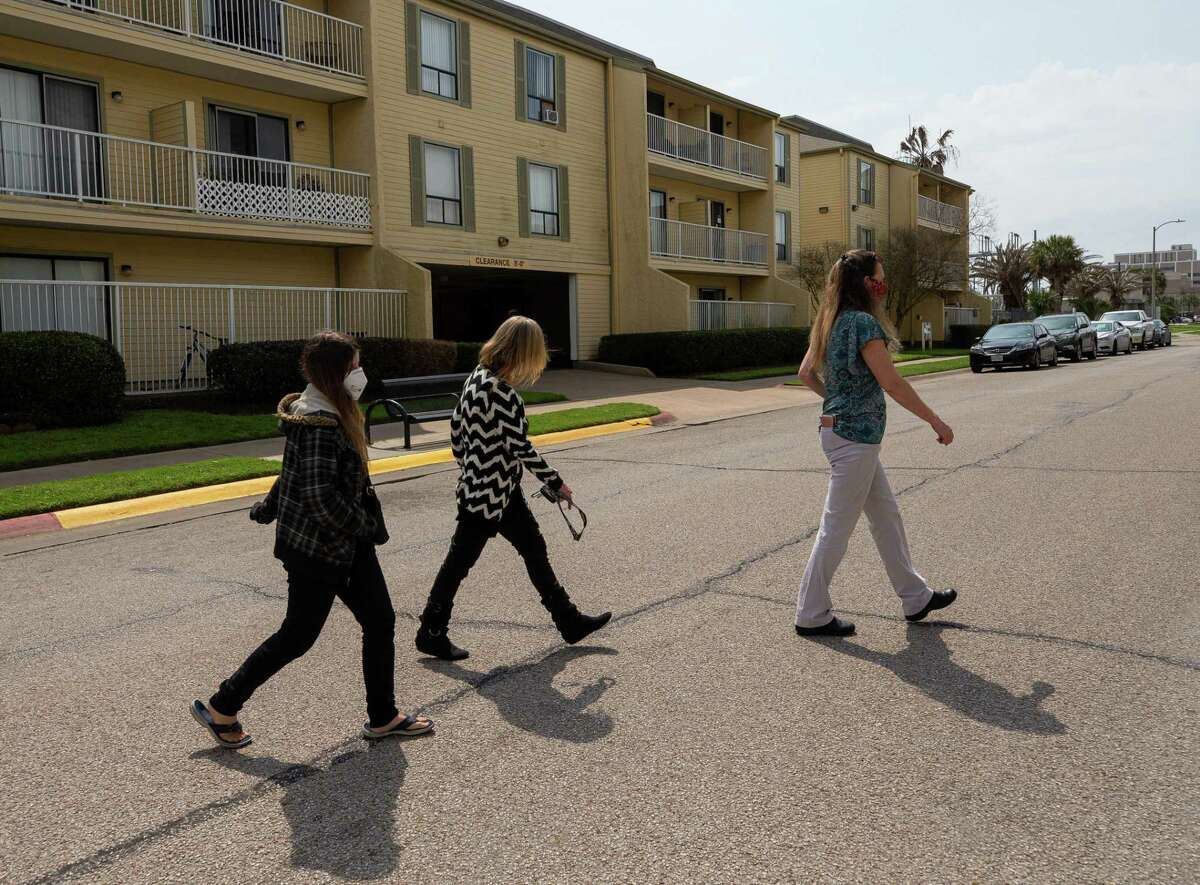 Aaliyah Lewis, left, and her mother Tina Harris walk with Carelton Courtyard Apartments manager Bonnie Nutt to their new apartment unit Tuesday, March 16, 2021, in Galveston, Texas.