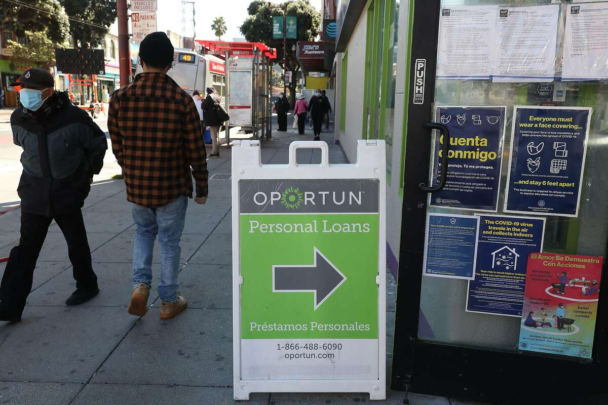 A sign advertises Oportun Inc. outside Milargos de Mexico on Mission Street. The financial lending company is under federal scrutiny for its collection practices against its mostly Latino clientele.