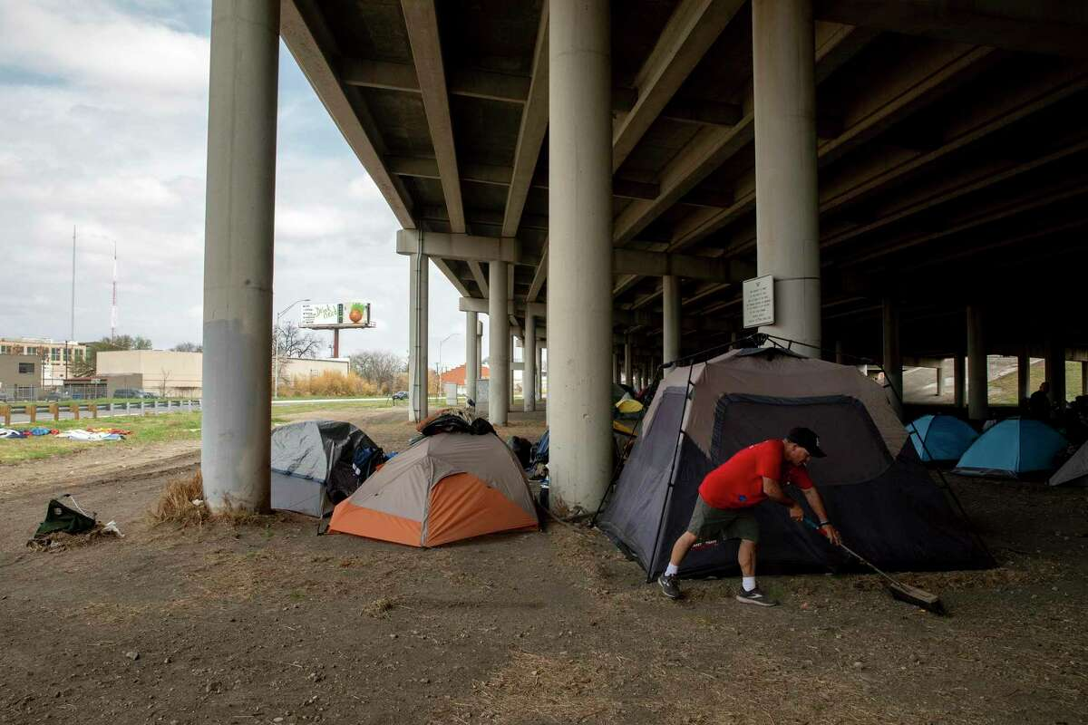 John Mellow sweeps the area around his friends' tents under the Interstate 37 overpass near McCullough, east of downtown San Antonio. Mellow says he does so to keep things as clean as possible and make living conditions just a little better. On March 16, 2021, word had spread that the encampment was to be removed soon, as it had been in early February.