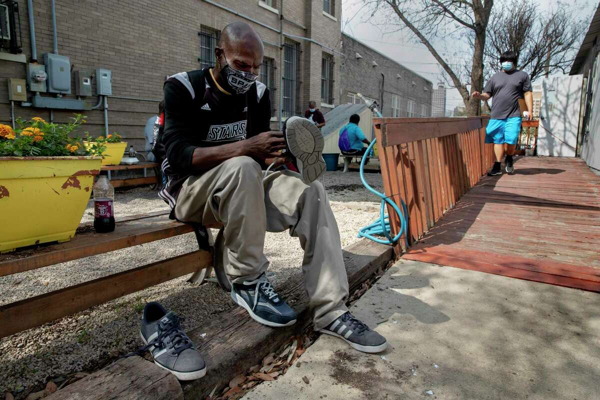 Andrew Wright, who has been living in a tent near the Interstate 37 overpass, tries on a new pair of shoes he received at an outreach event on March 16, 2021, at Christian Assistance Ministry near downtown San Antonio.