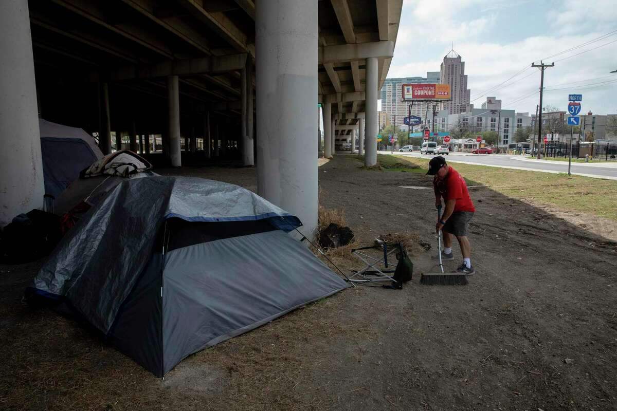 John Mellow sweeps the area around his friends' tents under the Interstate 37 overpass near McCullough, east of downtown San Antonio, on March 16, 2021. Mellow says he does so to keep things as clean as possible and make living conditions just a little better. Word had spread that the encampment was to be removed soon, as it had been in early February.