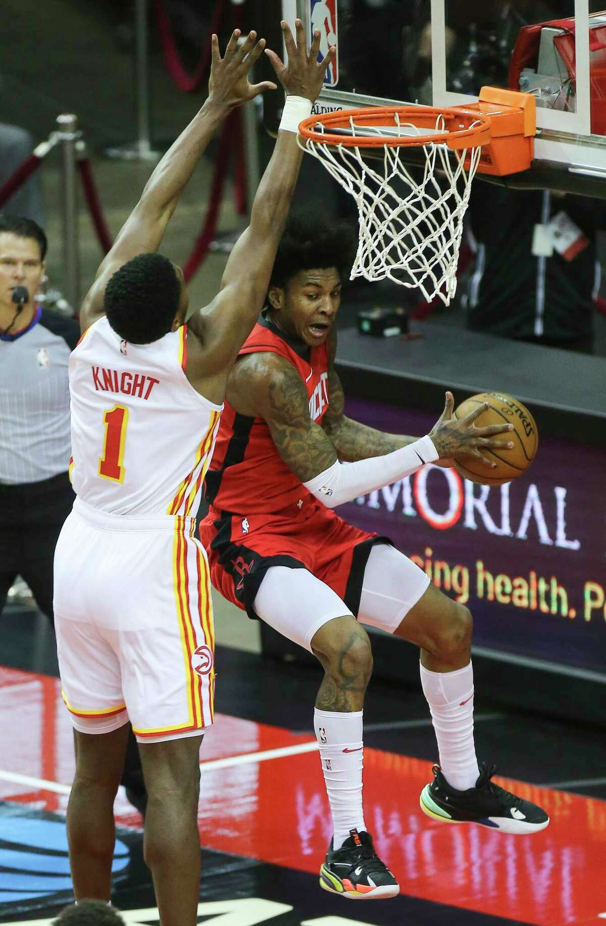 Houston Rockets guard Kevin Porter Jr. (3) attempts to score the basket under Atlanta Hawks forward Nathan Knight (1) during the first quarter of the NBA game Tuesday, March 16, 2021, at Toyota Center in Houston.