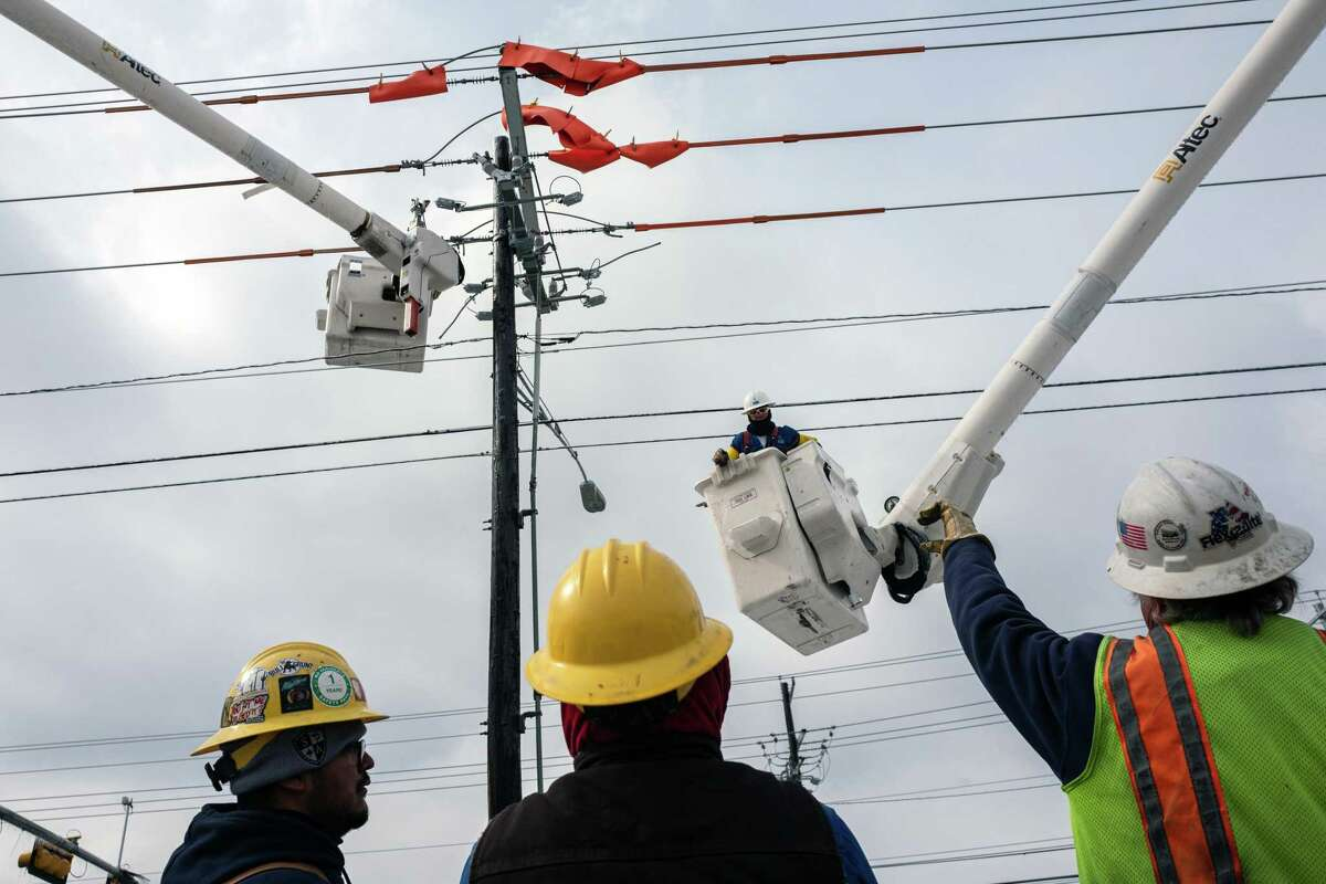 FILE -- Workers repair a utility pole after the winter storm in Austin, Texas, Feb. 18, 2021. The Electric Reliability Council of Texas decided to force out its chief executive on March 3 after the agency, which controls the flow of electricity through much of the state, became the target of blame and scorn for widespread outages during the February winter storm. (Tamir Kalifa/The New York Times)