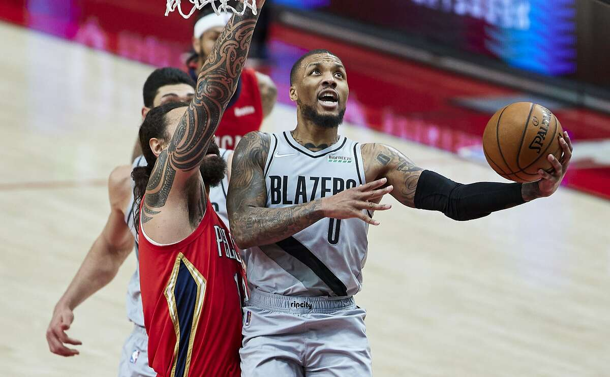 Portland Trail Blazers guard Damian Lillard, right, shoots next to New Orleans Pelicans center Steven Adams during the second half of an NBA basketball game in Portland, Ore., Tuesday, March 16, 2021. (AP Photo/Craig Mitchelldyer)