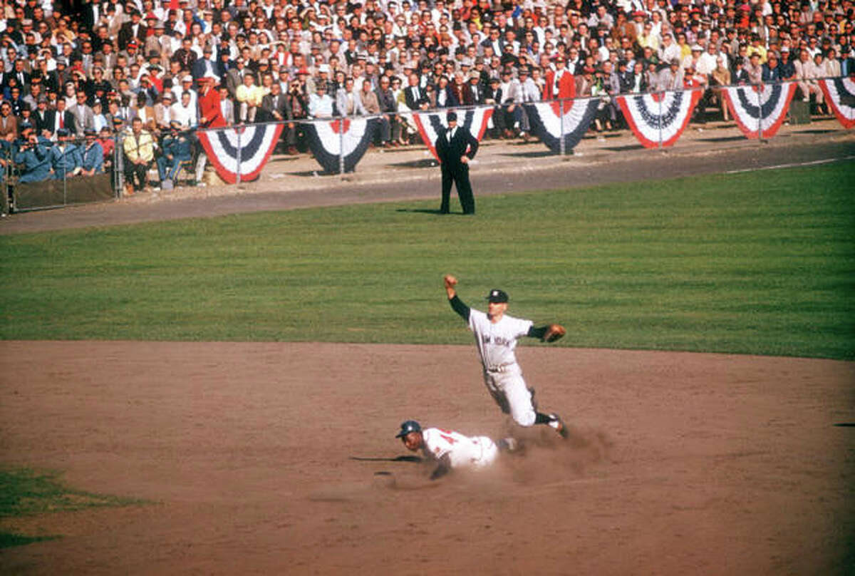 Hank Aaron slides into second base as Gil McDougald of the New York Yankees throws to first base during Game 5 of the 1957 World Series.