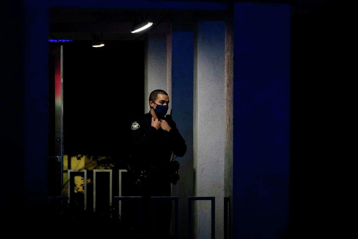 An officer stands outside Gold Spa after a shooting, late Tuesday, March 16, 2021, in Atlanta. Shootings at two massage parlors in Atlanta and one in the suburbs left multiple people dead, many of them women of Asian descent, authorities said. A 21-year-old man suspected in the shootings was taken into custody in southwest Georgia hours later after a manhunt, police said.