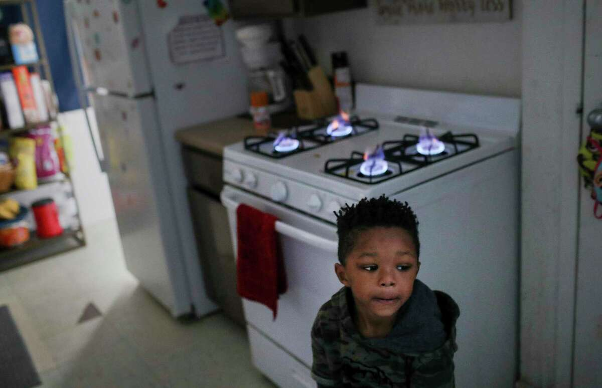 Kaiden Antoine, 3, stands by the stove, his family's only source of heat since their power went out, Tuesday, Feb. 16, 2021, at Cuney Homes in Houston.