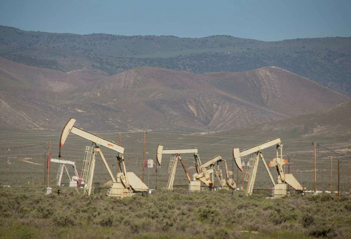 """MCKITTRICK, CA - APRIL 24: Oil pipelines, pumping rigs, and electrical transmission lines dot the landscape along California's """"Petroleum Highway"""" (Highway 33) running along the northwestern side of the San Joaquin Valley on April 24, 2020, near McKittrick, California.A private equity firm plans to acquire Enverus, the Austin-based global energy research firm providing data analytics to oil and gas companies."""