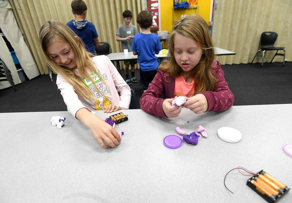 Kenleigh Harris (left) and Catherine Krause make light Play-do animals while learning about circuitry, part of their day of technology-themed activities during Beaumont Children's Museum's S.T.E.A.M. Camp, which began Monday. Each day of the camp will focus on five core concepts - science, technology, engineering, art and math. Small themed activities will be available to the public visitors daily, with all five concept activities on display Saturday. Photo made Tuesday, March 16, 2021 Kim Brent/The Enterprise