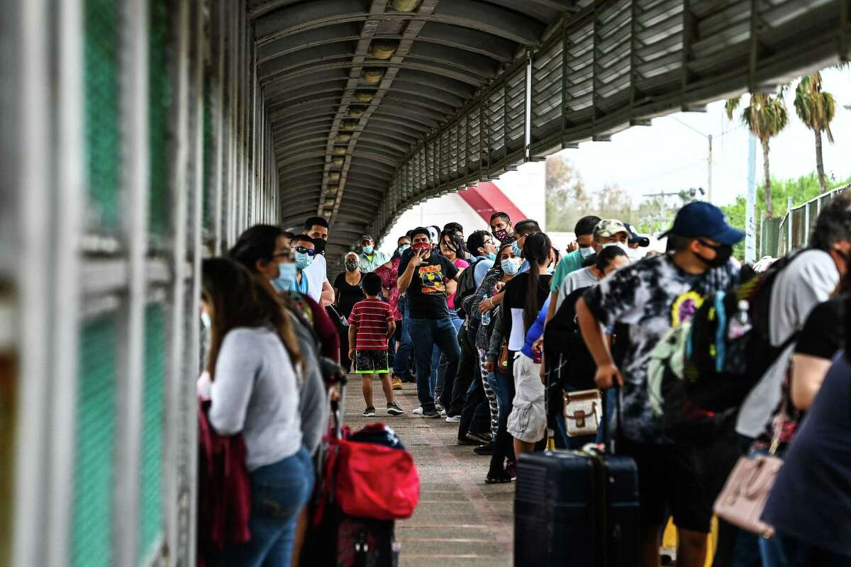 """Migrants mostly form Central America wait in line to cross the border at the Gateway International Bridge into the US from Matamoros, Mexico to Brownsville, Texas, on March 15, 2021. - It's the new normal for migrant families under President Joe Biden, after the harsh """"zero tolerance"""" approach of Donald Trump dashed the dreams of hundreds of thousands hoping to escape endemic poverty and violence in Central America. Biden's pledge of a more humane approach though has sparked a new rush to the border, threatening to become a huge political liability. Republicans are accusing him of opening the country's doors to illegal border-crossers and sparking a """"crisis"""" on the US-Mexico frontier, marked in Texas by the meandering Rio Grande river. (Photo by CHANDAN KHANNA / AFP) (Photo by CHANDAN KHANNA/AFP via Getty Images)"""