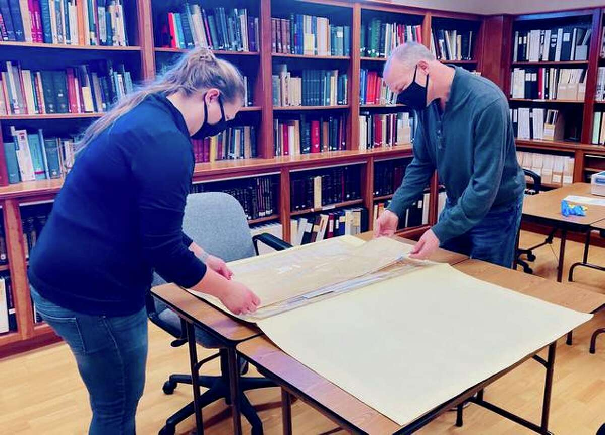 Jennifer VanBibber from the Madison County Historical Society and David Joens, director of the Illinois State Archives, examine Civil War documents related to the Alton Confederate Prison. The Historical Society recently donated the materials to the State Archives.