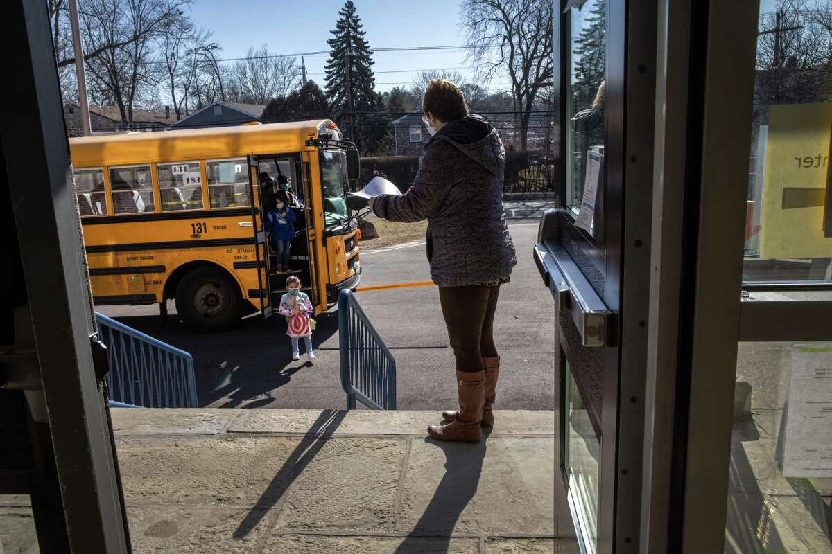 Students arrive for the first day of in-person learning for five days per week at Stark Elementary School on March 10, 2021 in Stamford, Connecticut.