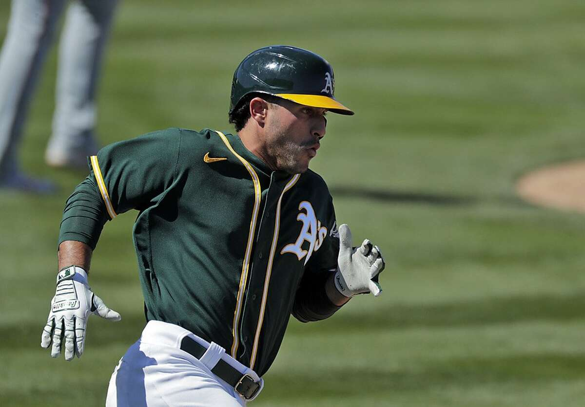 Ramon Laureano (22) rounds first base on a double in the second inning as the Oakland Athletics played the Los Angeles Angels at Hohokam Stadium in Mesa, Ariz., on Friday, March 5, 2021.