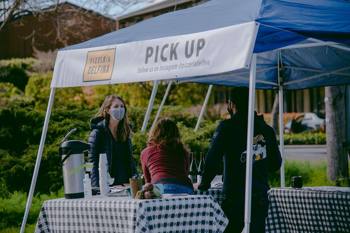 A customer picks up an online order from Pizzaria Delfina's SF2BAY pop-up in Mill Valley, Calif., on Saturday, March 13, 2021. SF2BAY is a food delivery service founded during the COVID-19 pandemic that brings beloved San Francisco restaurants to other regions in the Bay Area.