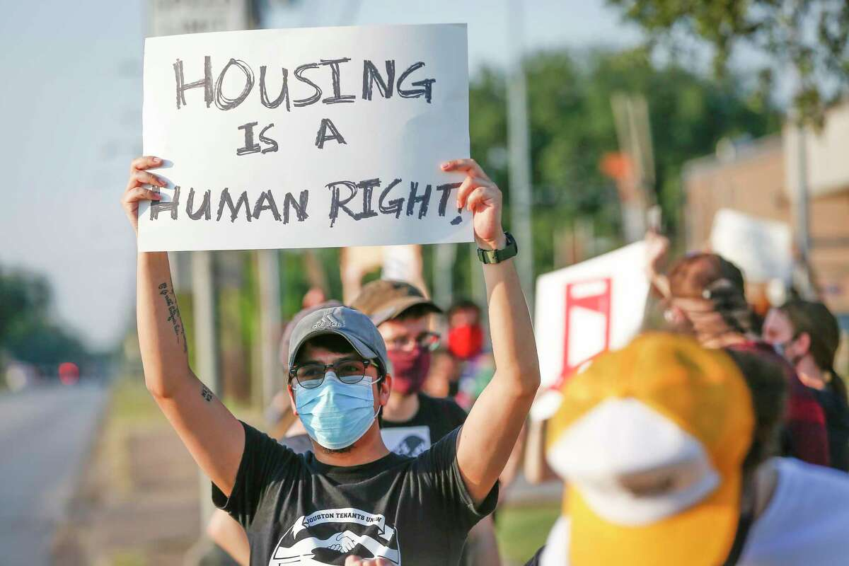 """""""Toby"""" holds a sign with other demonstrators during a protest regarding evictions going on at the court, 6000 Chimney Rock Road, Friday, Aug. 21, 2020, in Houston."""