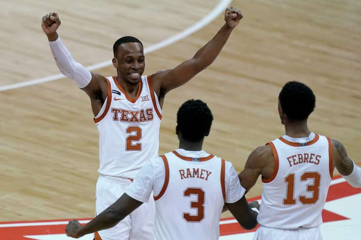 Texas' Matt Coleman III, center, celebrates with Courtney Ramey (3) and Jase Febres (13) after the team's win over Oklahoma State in an NCAA college basketball game for the championship of the Big 12 men's tournament in Kansas City, Mo, Saturday, March 13, 2021. (AP Photo/Charlie Riedel)