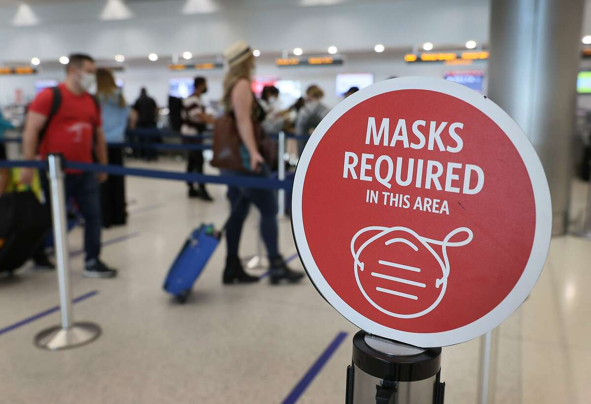 FILE A sign reading, 'masks required in this area,' is seen as travelers prepare to check-in on February 1, 2021 in Miami, Florida.