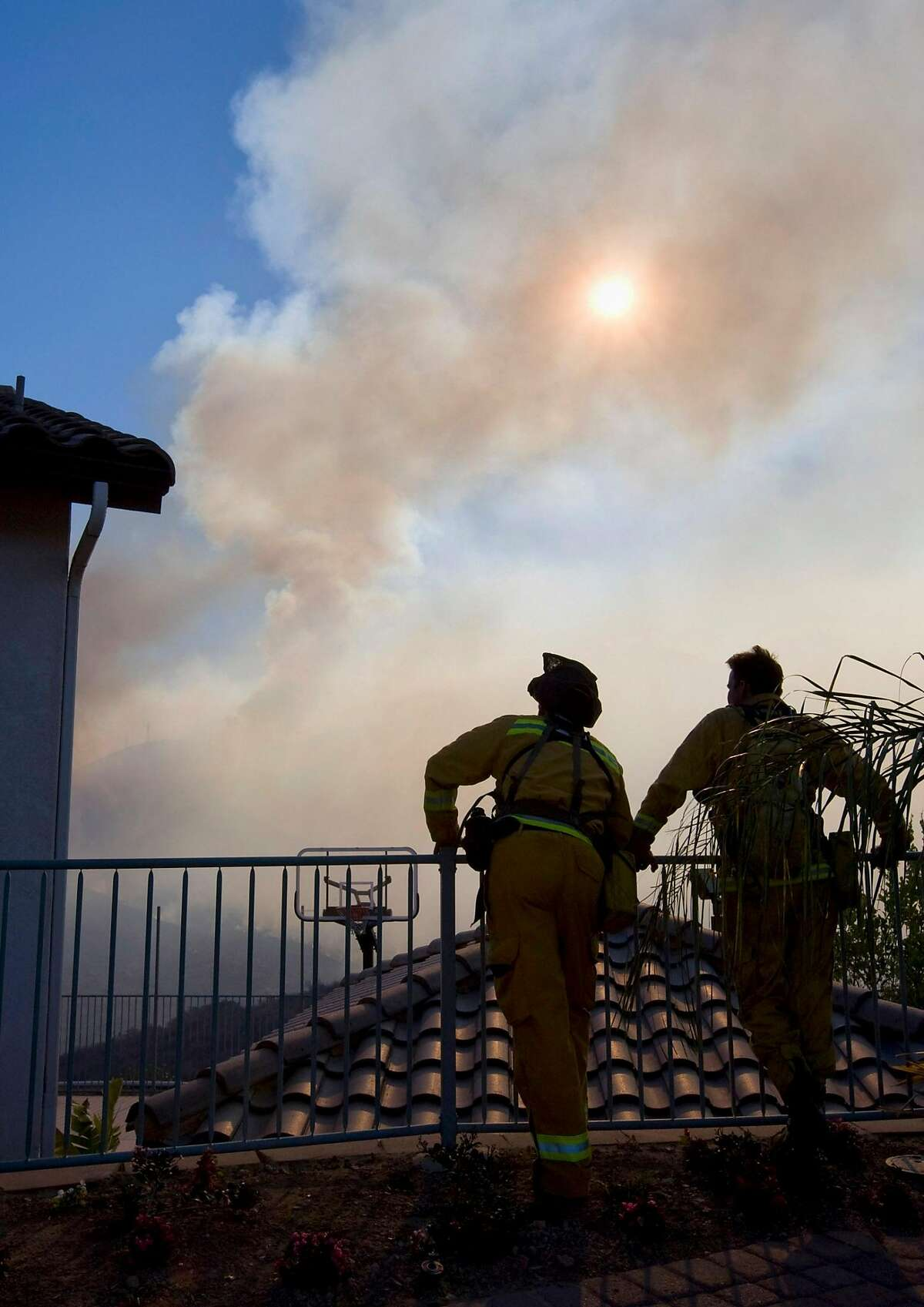 Firefighters watch the progress of the Harris Fire as it burns toward homes in Spring Valley (San Diego County) 2007. That fire burned part of the land where new development is planned. The state has joined lawsuits claiming the new projects weren't adequately reviewed.