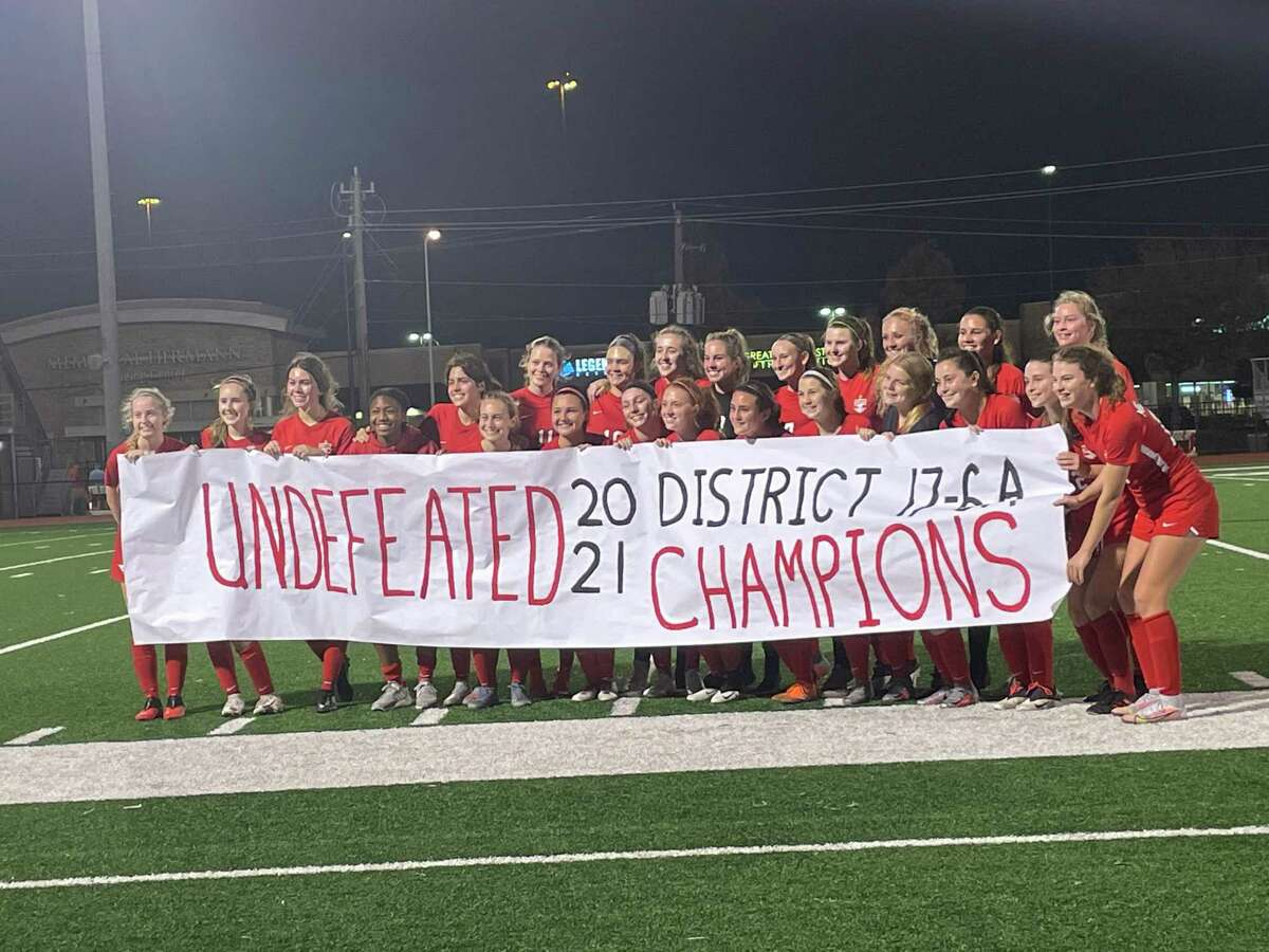 The Memorial girls soccer team celebrates an undefeated district championship after beating Cy Ridge 5-0 at home on March 12 in the final district game