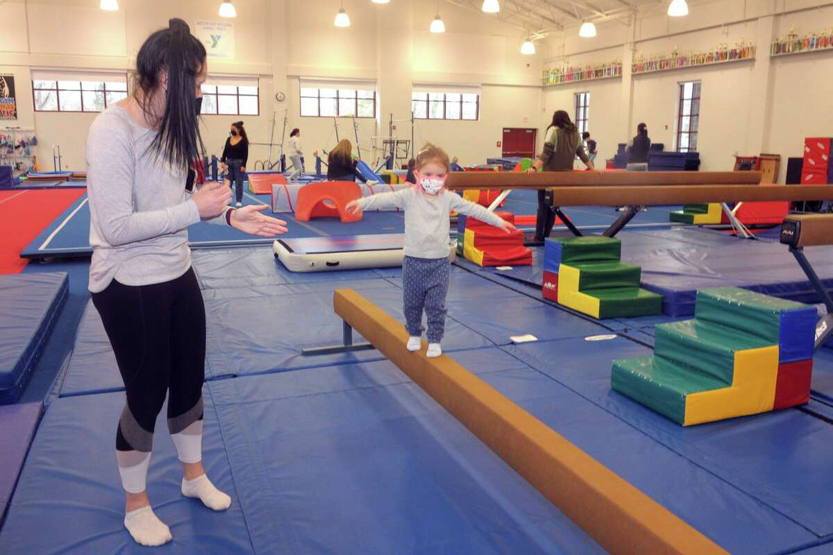 Eliza Carey walks on a balance beam in the company of her au pair, Bernelee Kritzinger, during a visit to the gymnasium of the Westport Weston Family YMCA in Westport on Tuesday.